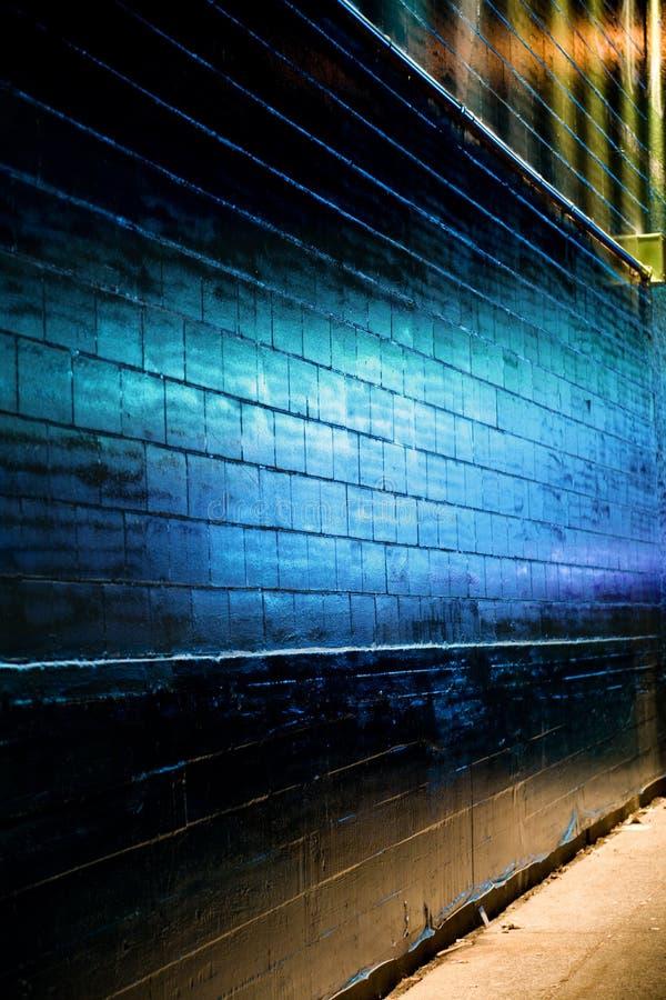 La luz azul refleja en la pared de ladrillo imágenes de archivo libres de regalías