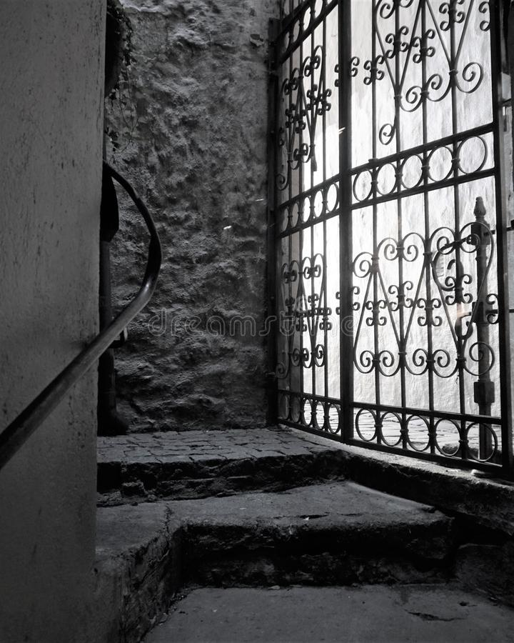 La luz brilla a través de puerta obstruida del arrabio en el paso de piedra imagen de archivo