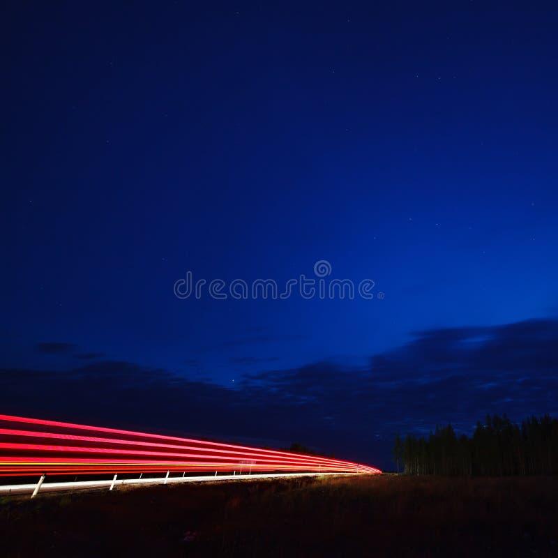 La luz de los coches en la carretera en el cielo estrellado de la noche foto de archivo libre de regalías