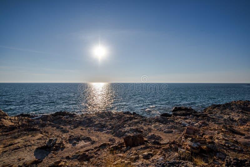 La luz de Sun con la sombra en onda del mar detrás de la roca y la arena apuntalan imagen de archivo