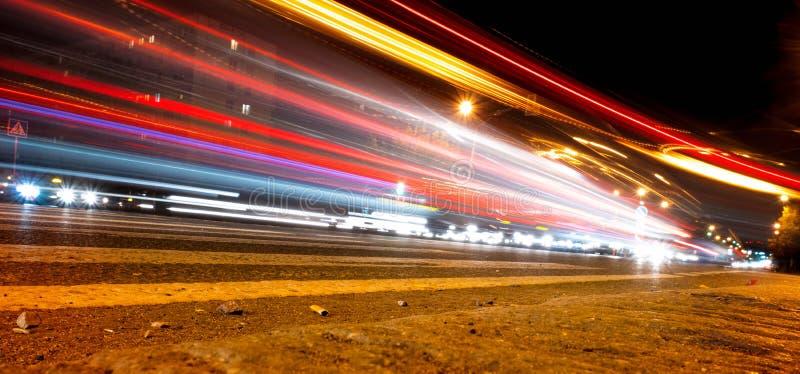 La luz del coche se arrastra en la calle cerca del puente del camino, gente que camina en el movimiento rápido, fondo de la calle fotos de archivo