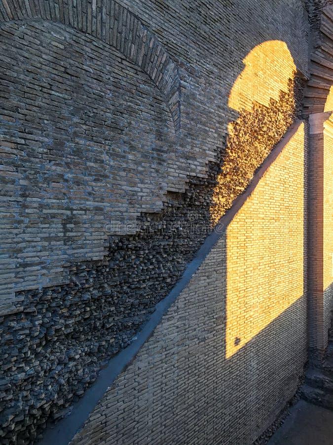 La luz del sol a través de un arco de Colosseum refleja en un insid de la pared de ladrillo fotos de archivo