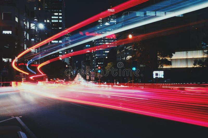 La luz del tráfico fluye por la avenida de la ciudad foto de archivo libre de regalías