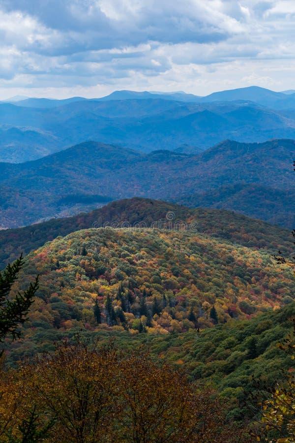 La luz destaca una montaña más baja cubierta en colores de la caída fotografía de archivo libre de regalías