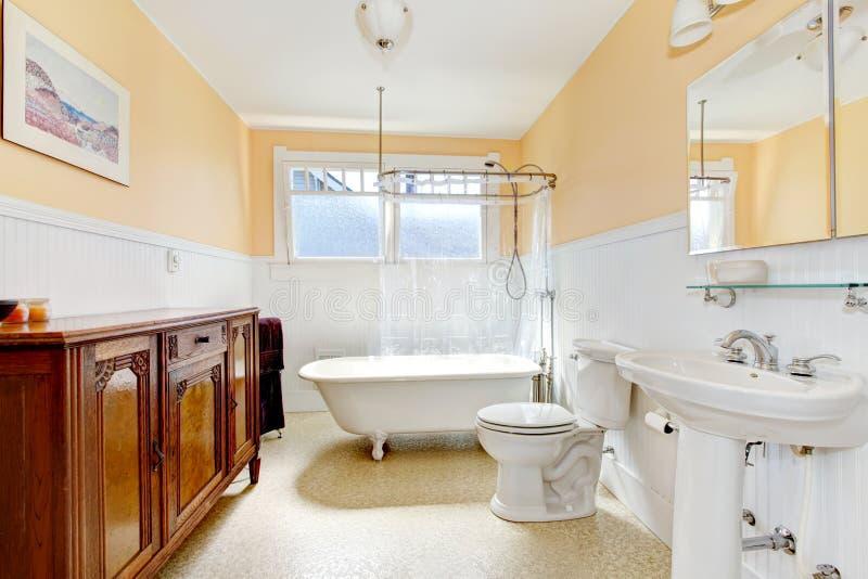 La luz entona el pequeño cuarto de baño con un gabinete de la antigüedad del color del whisky imagen de archivo libre de regalías