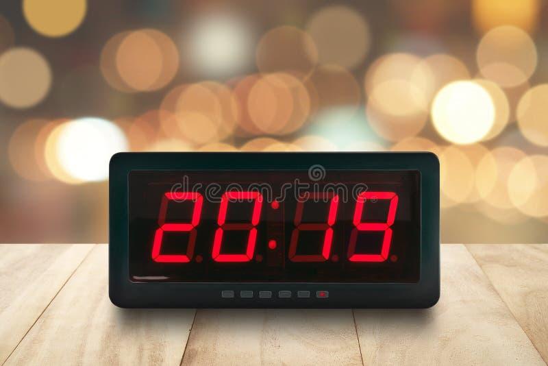 La luz llevada roja iluminó los números 2019 en cara digital del despertador en la tabla de madera con el bokeh colorido defocuse foto de archivo
