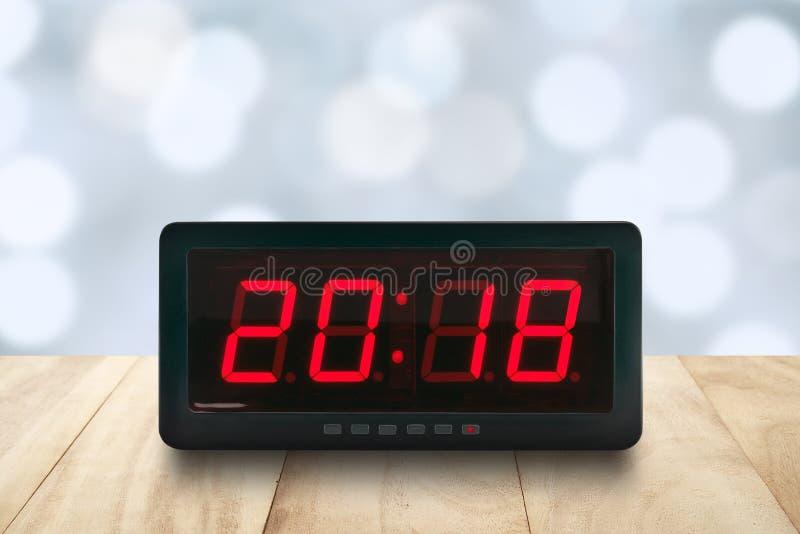 La luz llevada roja iluminó los números 2018 en cara eléctrica digital del despertador en la sobremesa de madera con el bokeh azu imagenes de archivo