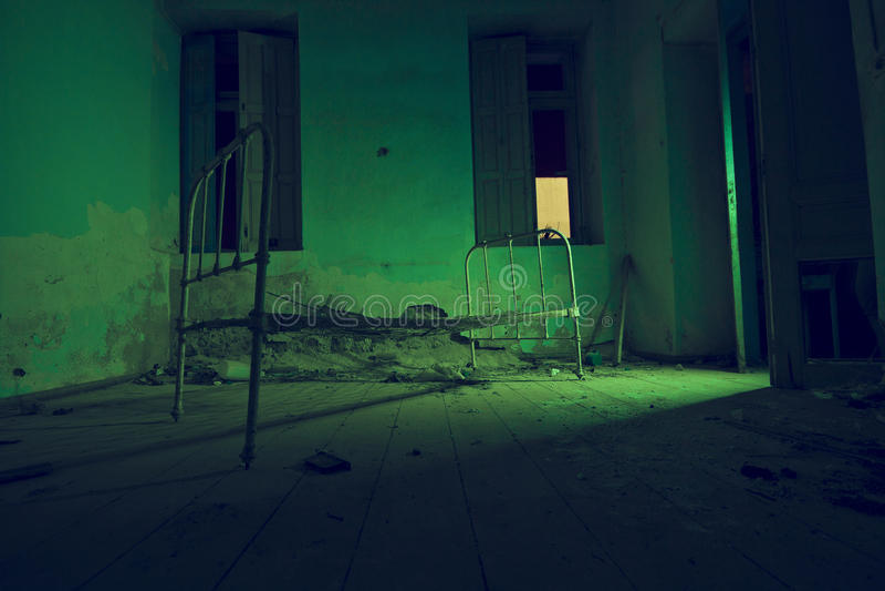La luz pintada en verde abandonó la cama en sitio oscuro imagen de archivo