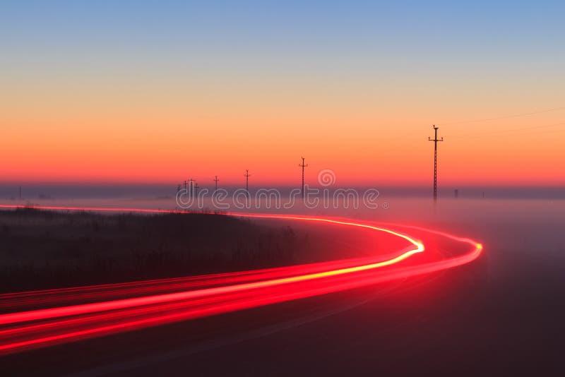 La luz roja del coche de la exposición larga se arrastra en un camino afuera en la noche de niebla en hora azul foto de archivo libre de regalías