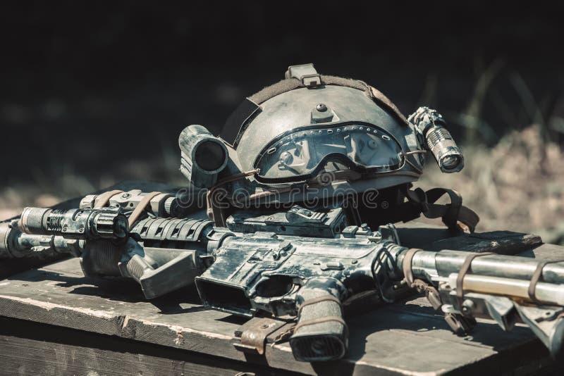 La máquina, ametralladora, casco del ejército con una linterna que miente en una pila en una caja de madera de munición imagen de archivo libre de regalías