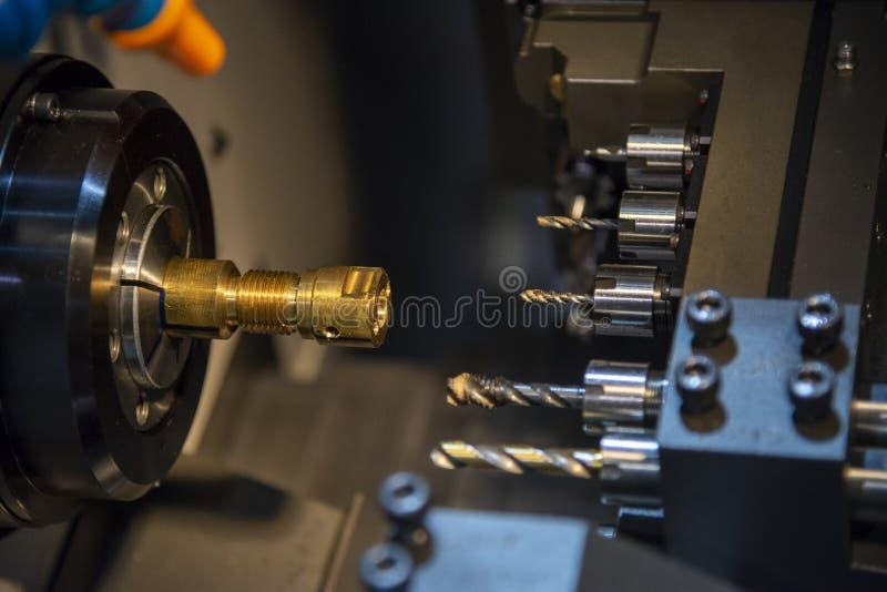 La máquina CNC traza en proceso de golpeado metálico a las piezas del eje de latón con las herramientas de golpeado fotos de archivo