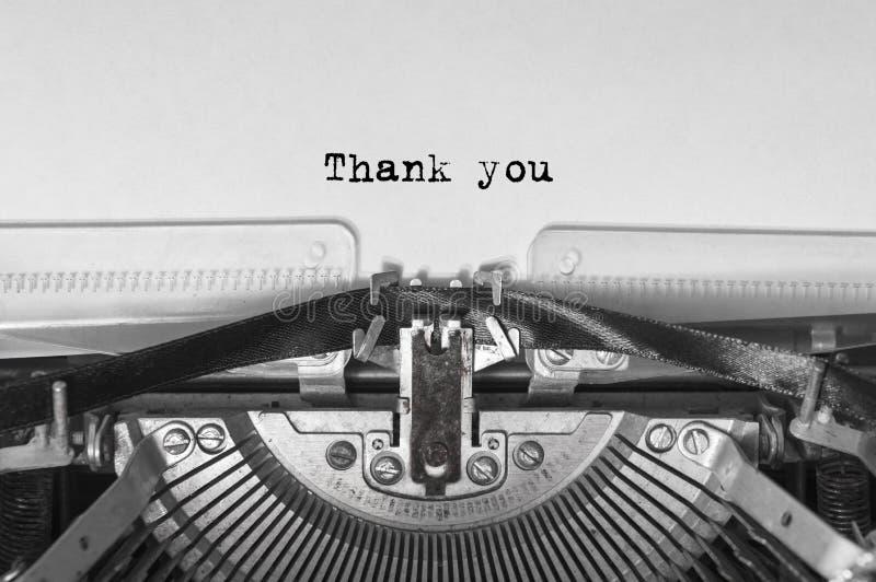 La máquina de escribir vieja del vintage en el fondo blanco con el texto le agradece Cierre para arriba imagenes de archivo