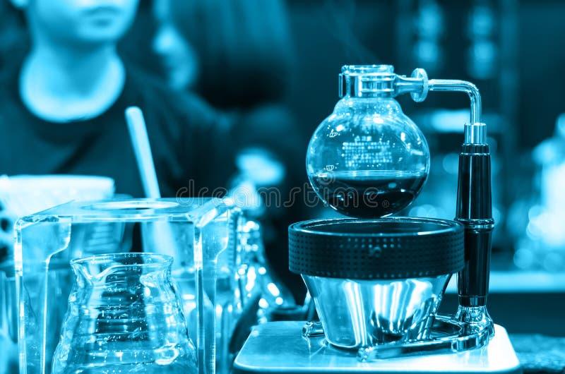 La máquina del café en tienda con el cliente empañó el fondo fotografía de archivo