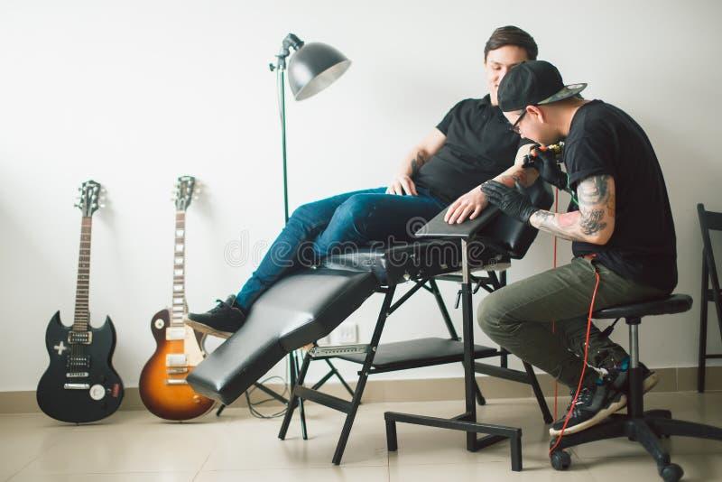 La máquina del tatuaje hace el dibujo en la mano masculina imagen de archivo