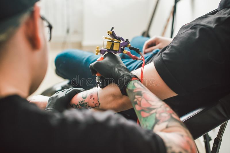 La máquina del tatuaje hace el dibujo en la mano masculina foto de archivo libre de regalías