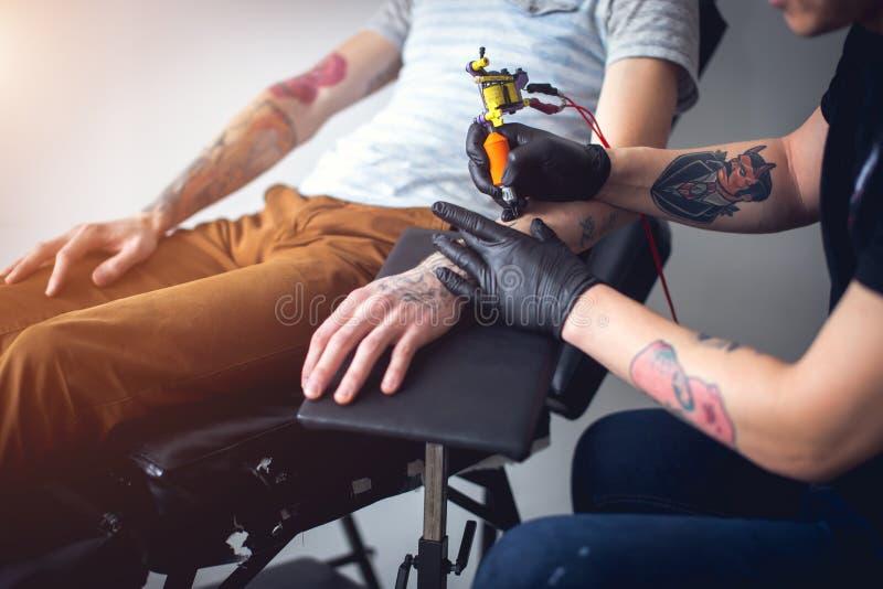 La máquina del tatuaje hace el dibujo en la mano masculina imagen de archivo libre de regalías