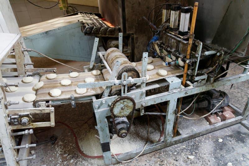 La máquina vieja para formar la pasta junta las piezas en una banda transportadora para la producción de flatbread árabe en una p fotografía de archivo