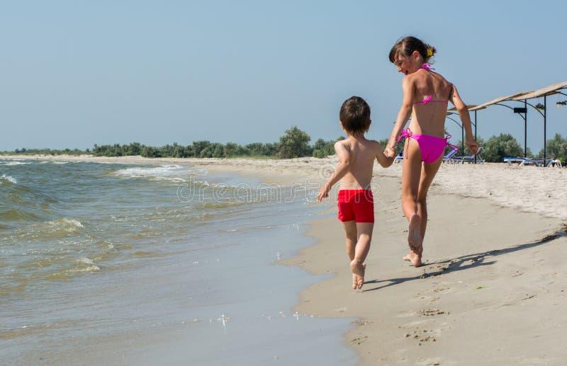 La más vieja hermana con su hermano menor que corre alrededor de la playa que lleva a cabo las manos imagenes de archivo