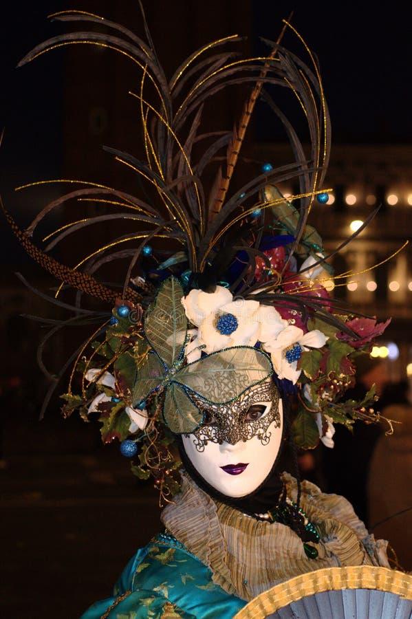 La máscara con el sombrero de flores y de plumas en el carnaval de Venecia fotografía de archivo