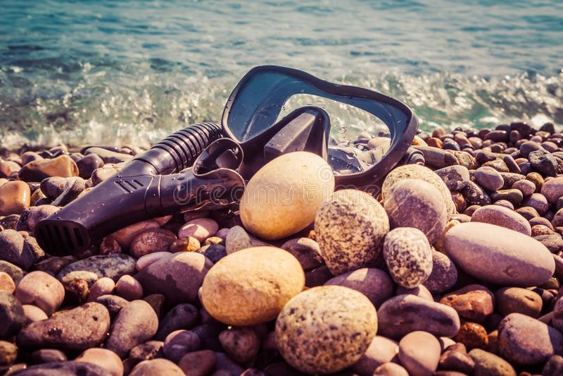 La máscara negra para zambullirse y un tubo para respirar bajo mentira del agua en la orilla contra la perspectiva del mar agita  fotografía de archivo