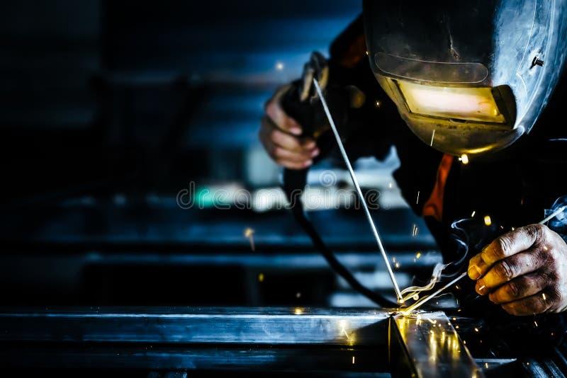 La máscara profesional protegió al hombre del soldador que trabajaba en la soldadura del metal y chispea el metal fotografía de archivo
