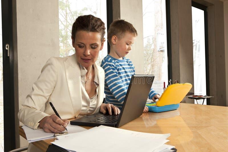La mère écrit à côté de l'ordinateur image stock
