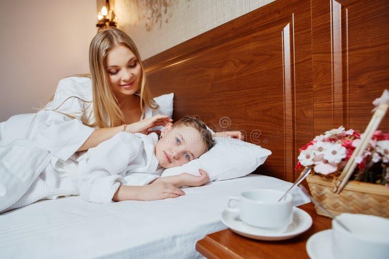 La mère affectueuse repasse la fille se situant dans un lit sur la tête image libre de droits