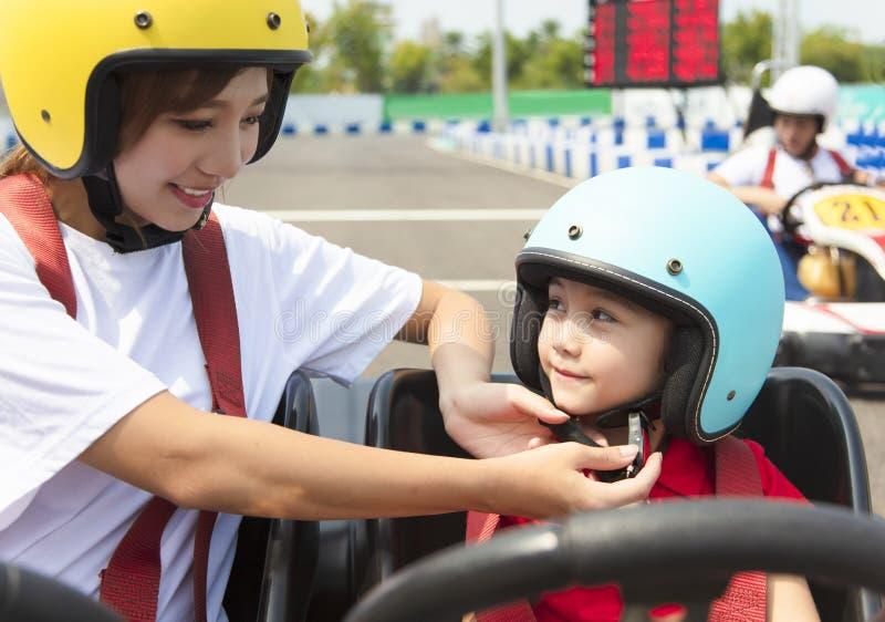 La mère attachant le casque de filles vont dessus kart photographie stock