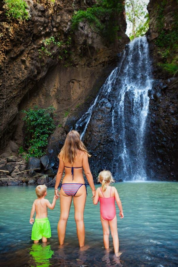 La mère avec des enfants nagent dans la piscine d'eau sous la cascade photo stock
