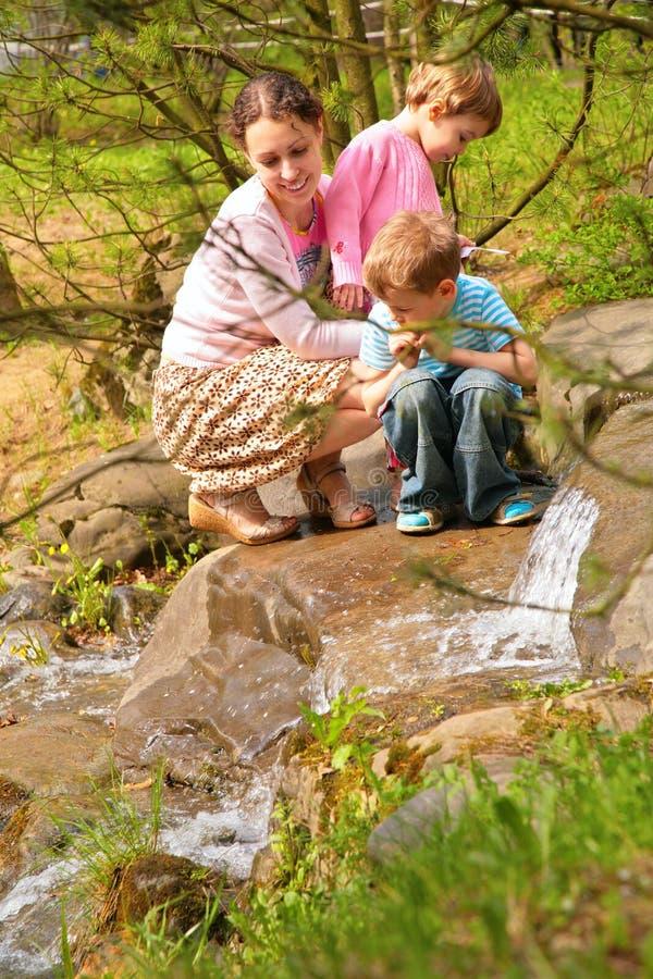 La Mère Avec Des Enfants Regardent Sur Peu De Cascade à écriture Ligne Par Ligne Photo stock