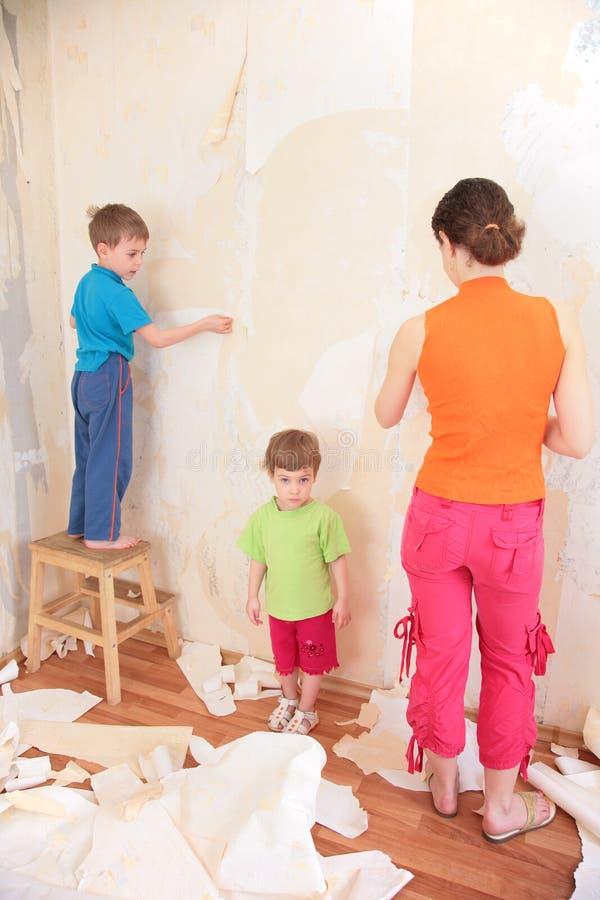 La mère avec des enfants retirent de vieux papiers peints du wa photo stock
