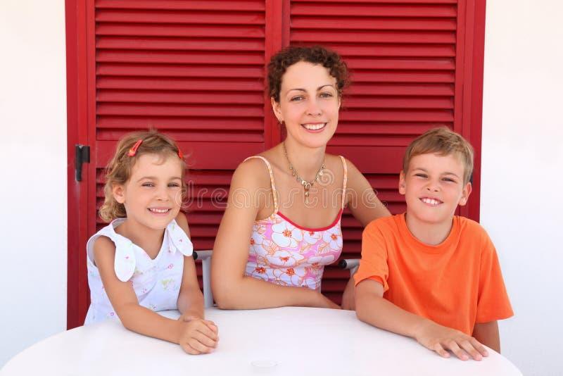 La mère avec des enfants s'asseyent près de la trappe fermée pour ajourner photo stock