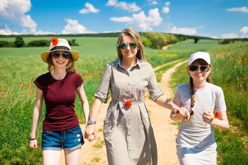 La m?re avec la fille ayant des fleurs de pavot marchent sur la route de chariot photos libres de droits