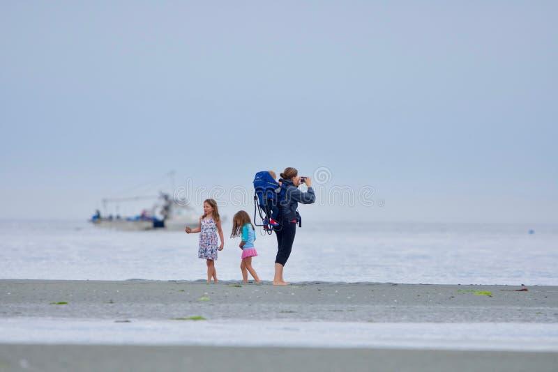 La mère avec l'enfant en bas âge et deux jeunes filles apprécient la plage à la lagune pleine d'esprit à marée basse image libre de droits