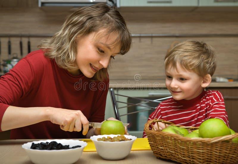 La mère avec l'enfant est fruit mangé photo libre de droits