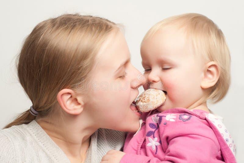 La mère avec le descendant mangent et pain d'épice bitting images stock