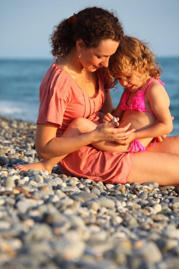 La mère avec le descendant s'assied sur le littoral image libre de droits
