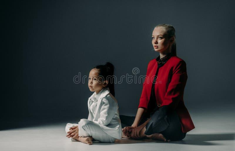 La mère avec sa fille s'asseyent sur le plancher dans la pose du yoga images libres de droits
