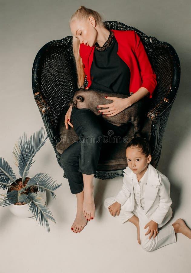 La mère avec sa fille s'assied dans le fauteuil et tient le viet photographie stock libre de droits