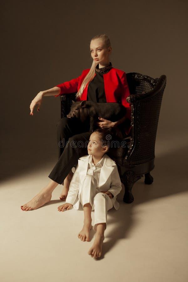 La mère avec sa petite fille s'assied dans le fauteuil et le holdi photo libre de droits