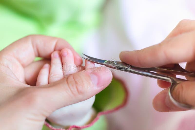 La mère coupe les clous minuscules d'une manière ordonnée et doucement sur la main de nouveau-né utilisant des ciseaux de clou Co images libres de droits