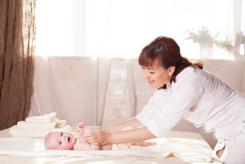 La mère de bébé de petit garçon faisant des mains et des jambes de massage photo libre de droits