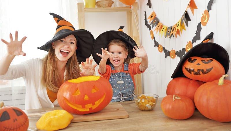 La mère de famille et la fille d'enfant dans la sorcière de chapeau se préparent à image libre de droits
