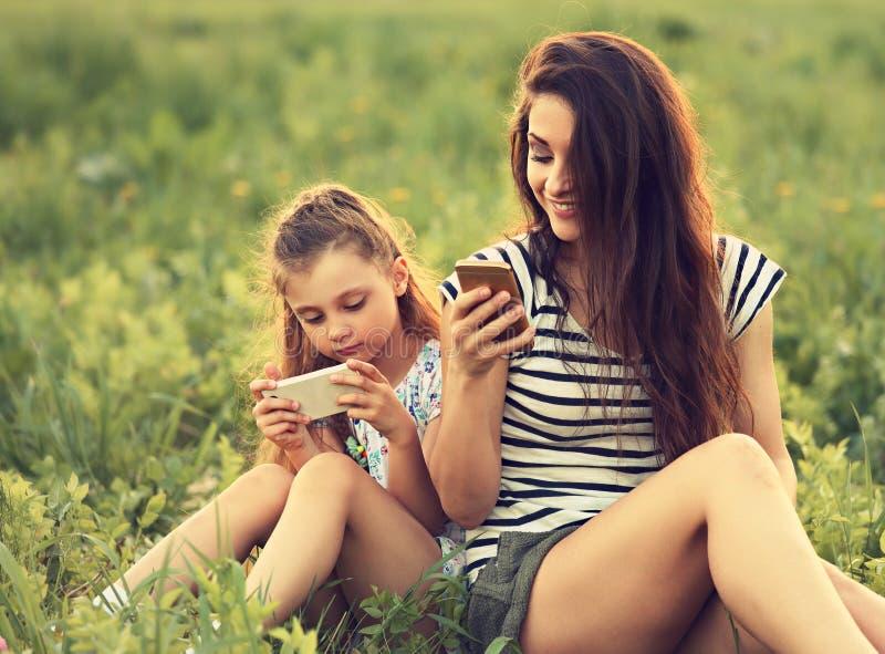 La mère de sourire heureuse et l'amusement badinent la fille s'asseyant sur le verre vert et photo libre de droits