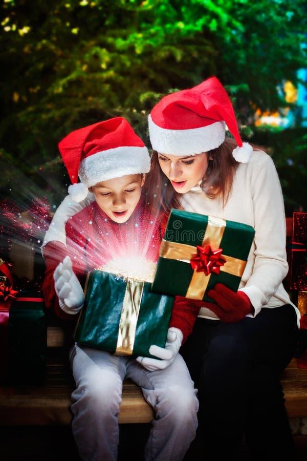 La mère donne à son enfant un boîte-cadeau de Noël avec les rayons légers et images stock