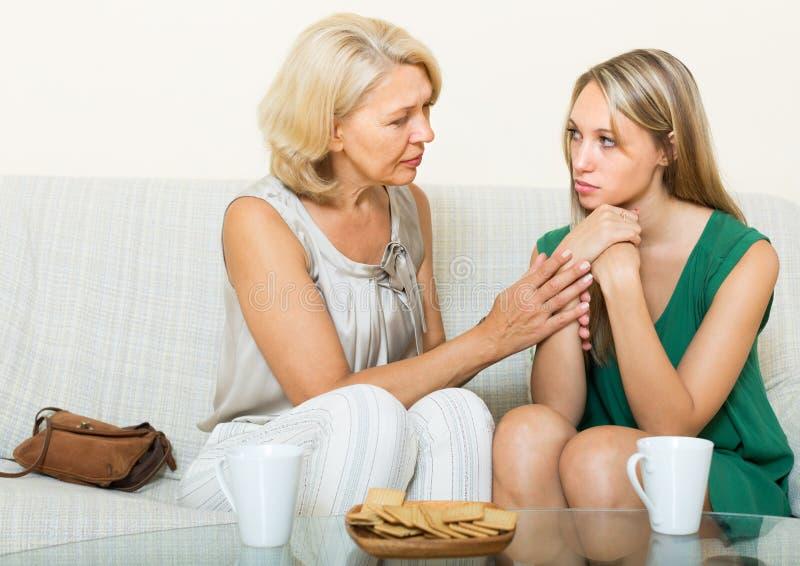 La mère donne la consolation à la fille photographie stock