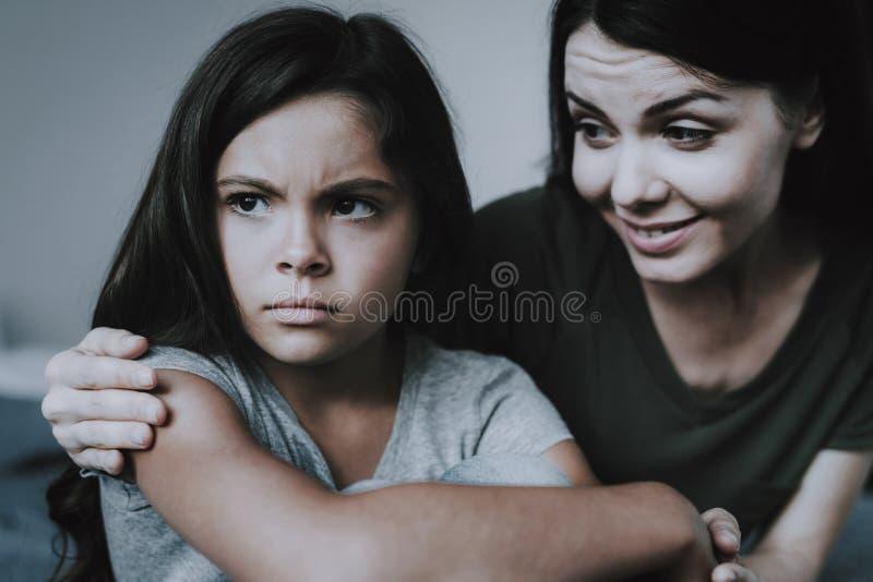 La mère embrasse la fille indifférente et les sourires image libre de droits