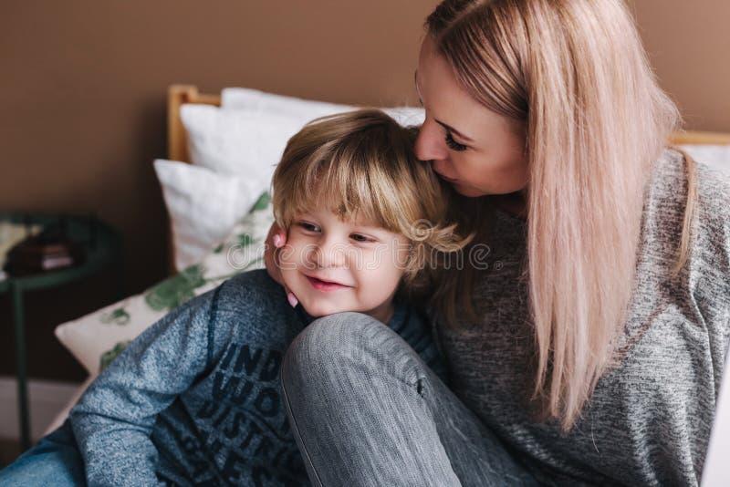La mère embrasse son fils Maman et fils Jour heureux du `s de mère Mère étreignant son enfant à la maison photos libres de droits
