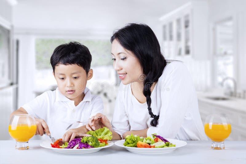 Encouragez l'enfant à manger de la salade à la maison photos stock
