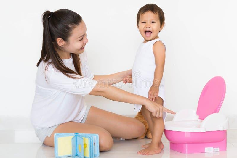 La mère enseigne avec succès la formation de pot d'enfant images stock